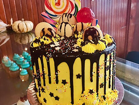 yellow cake with chocolate dripping and lollipops