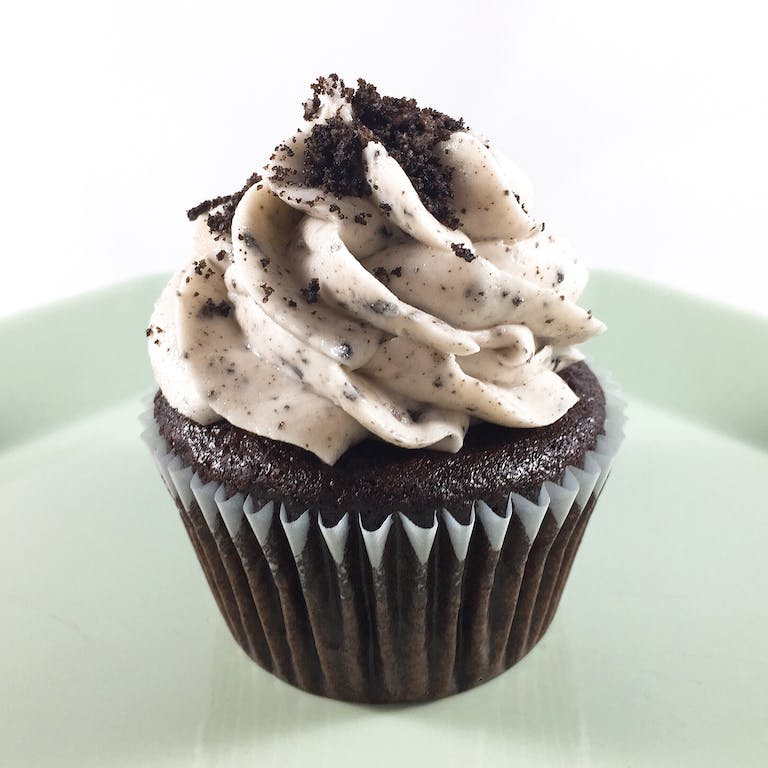 Chocolate cupcakes baked with an oreo cookie, topped with cookies n'cream cream cheese frosting and Oreo cookie crumbles