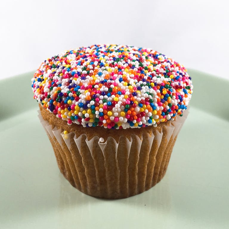 Vanilla cupcakes topped with buttercream and dipped in rainbow sprinkles