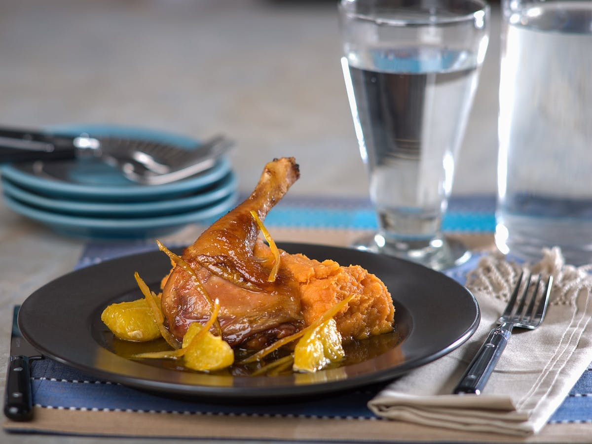 a plate of chicken sided by a glass of water