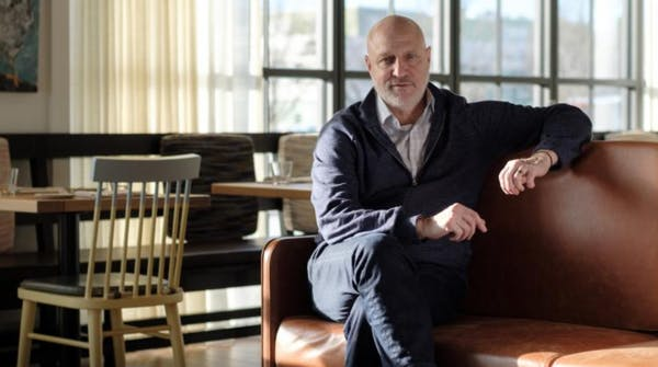 Tom Colicchio sitting on a chair in front of a window