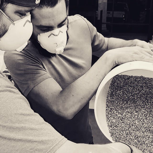 two men pouring seeds on a bottle