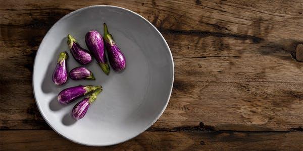 Fresh Eggplant on White Plate