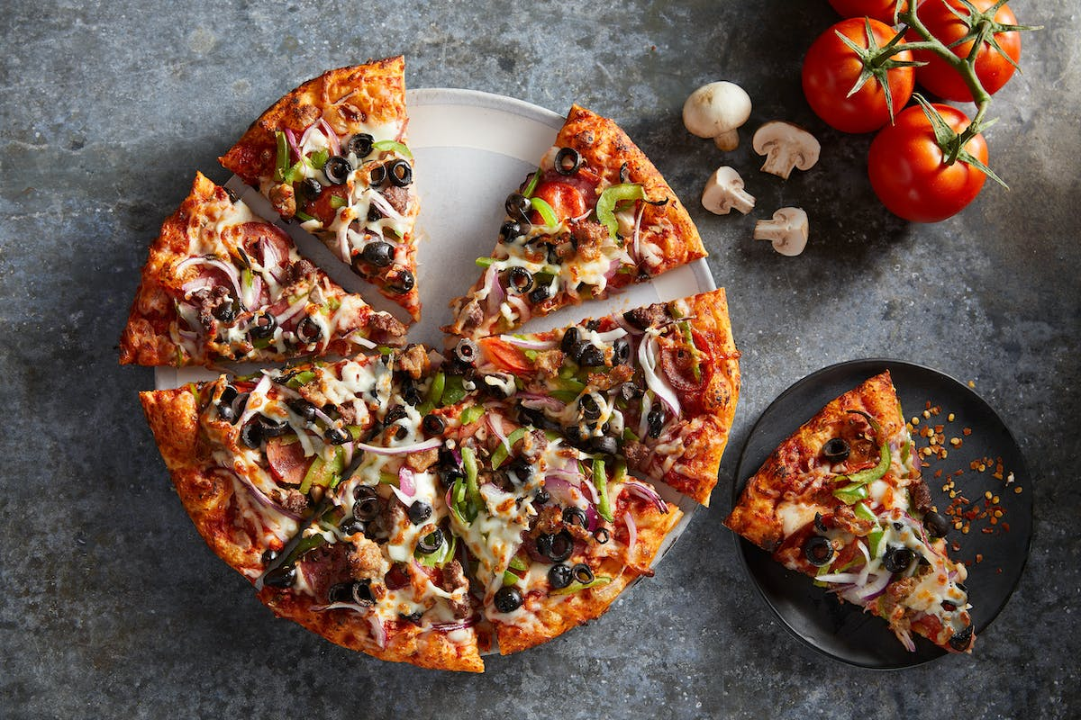 a pizza on a tray and a slice of pizza on a plate