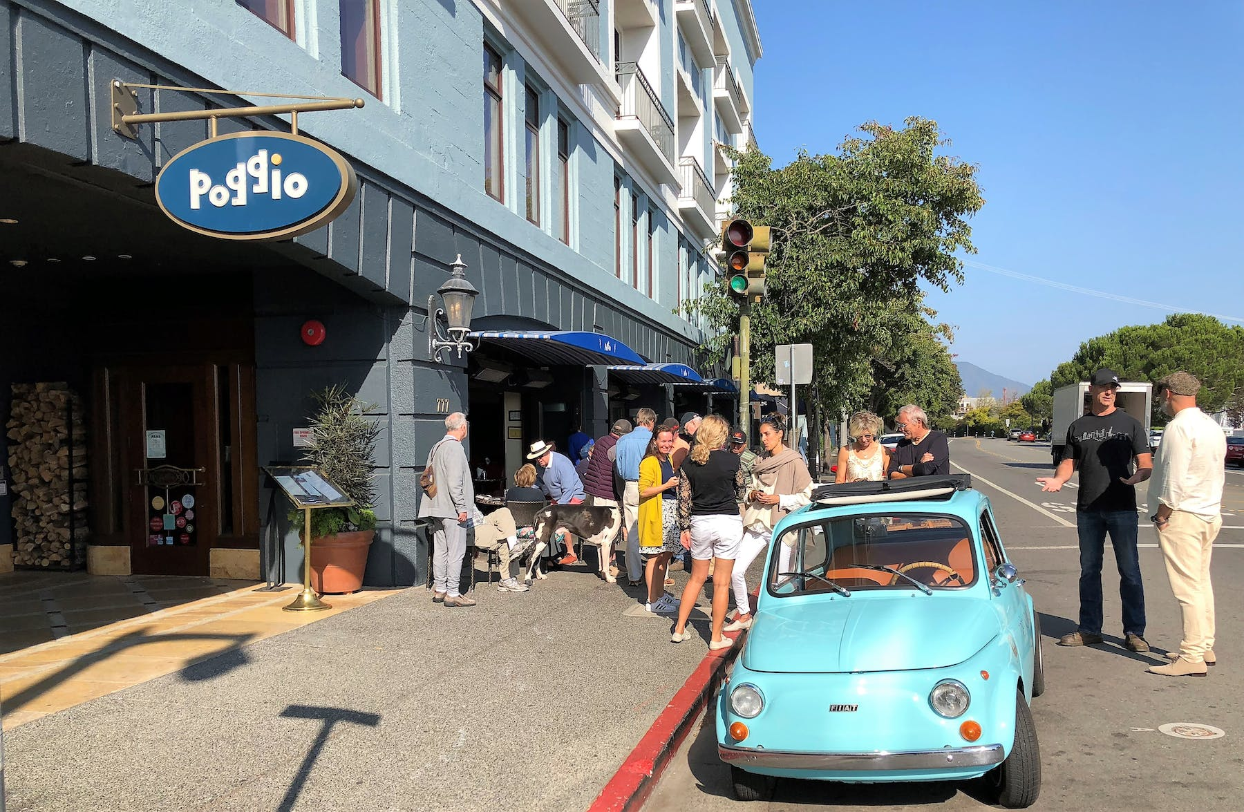 a car parked outside a building, and people on the sidewalk.