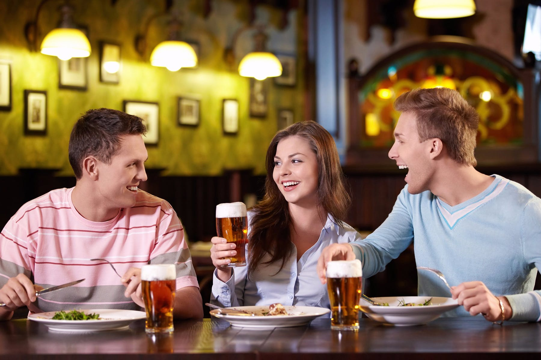 three people sitting down at a table drinking beer