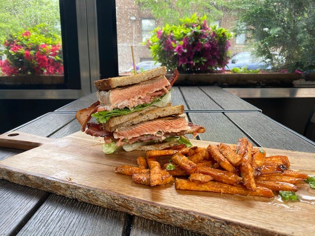a sandwich sitting on top of a wooden cutting board
