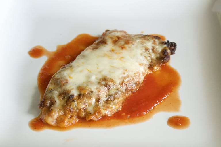 A piece of Chicken with cheese and sauce
