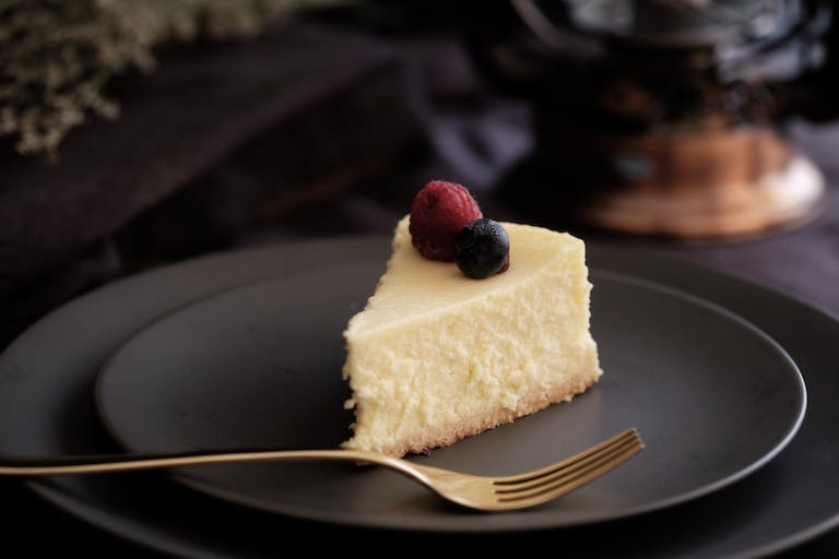 a close up of a piece of cheesecake on a plate