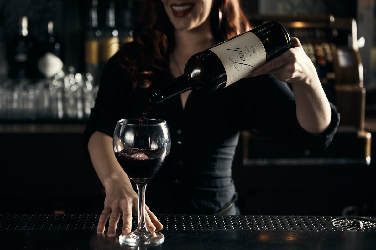 a person serving a glass of wine