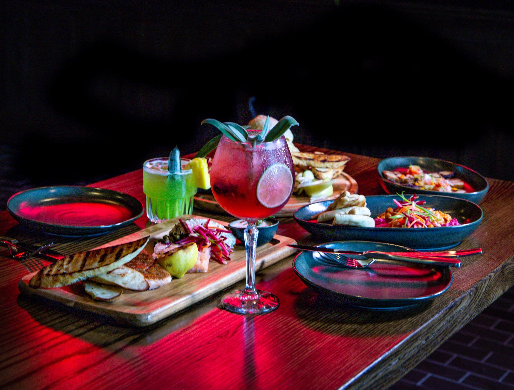 a table topped with a red tablecloth, plates of food and glasses of wines