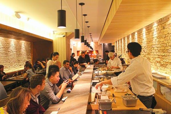 People eating inside JaBistro sushi restaurant while chefs make food
