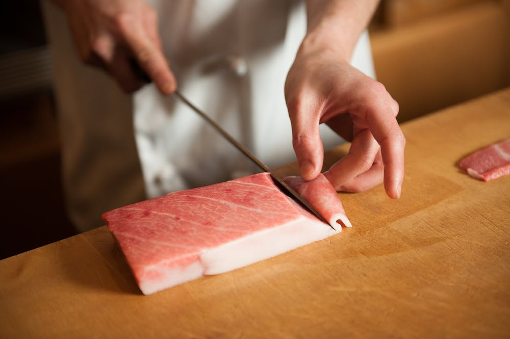 a knife on a cutting board with a cake