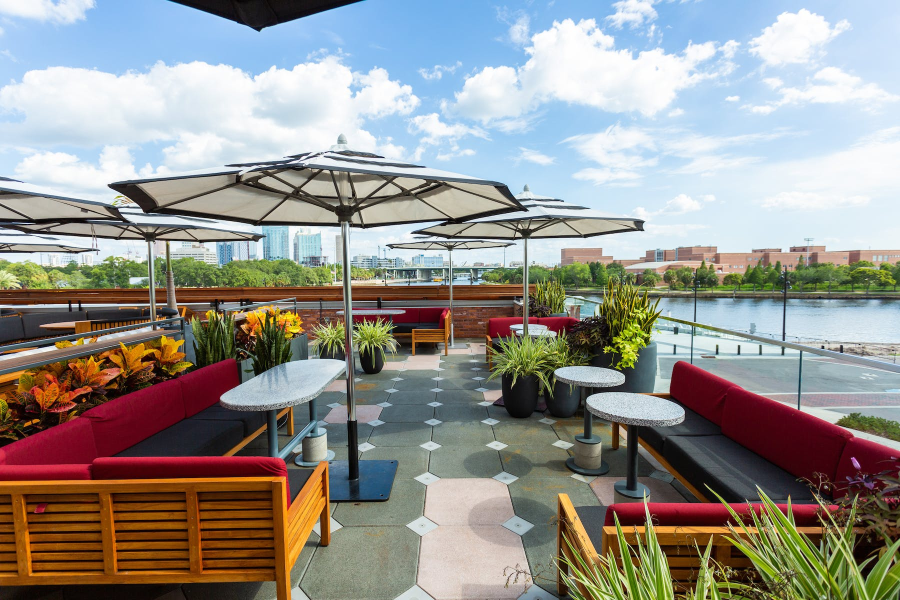 bar tables with booth seating under umbrellas in a corner overlooking the Hillsborugh River