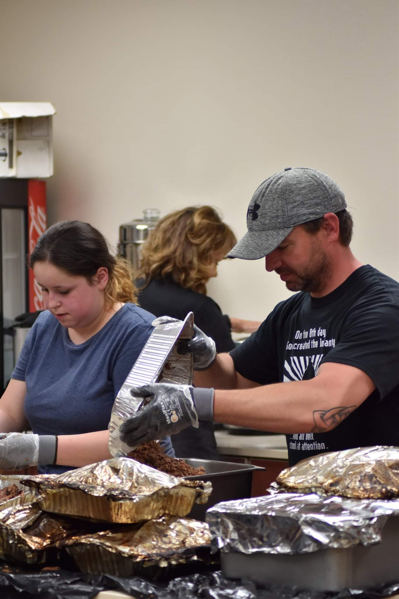 a man and woman cooking food on a table