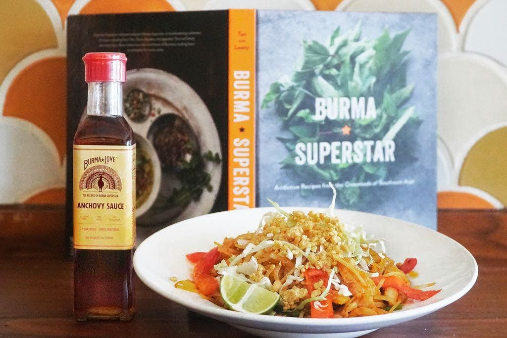 A bottle of anchovy sauce and a bowl of spicy noodles in front of a Burma Superstar cookbook. fish sauce