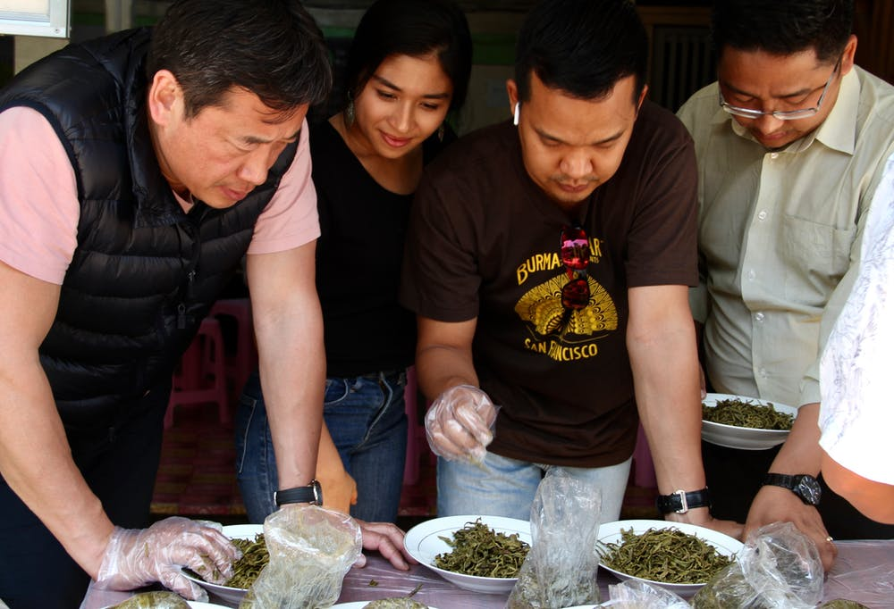 a group of people preparing food on a table