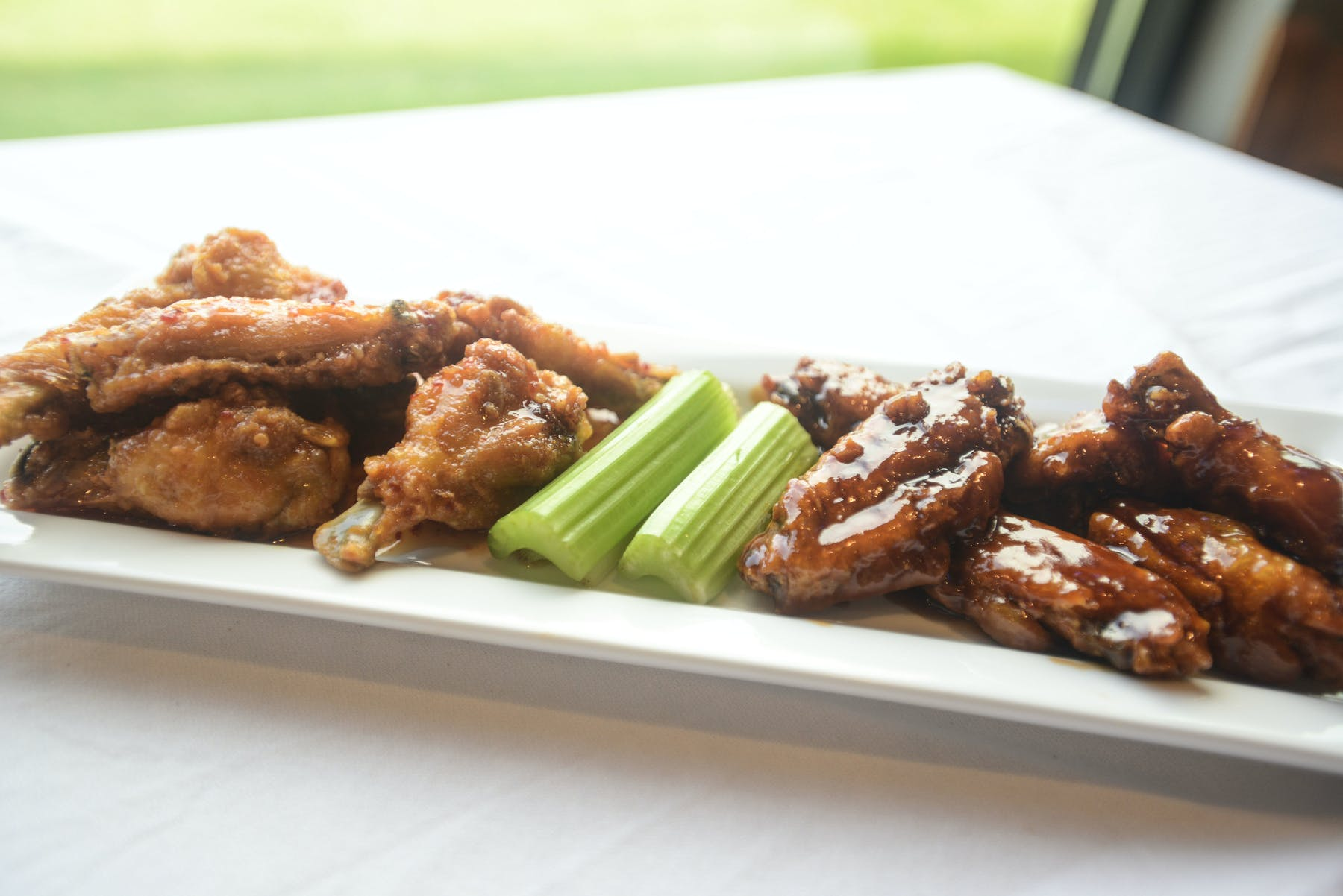 a white long rectangular plate topped with buffalo and BBQ wings