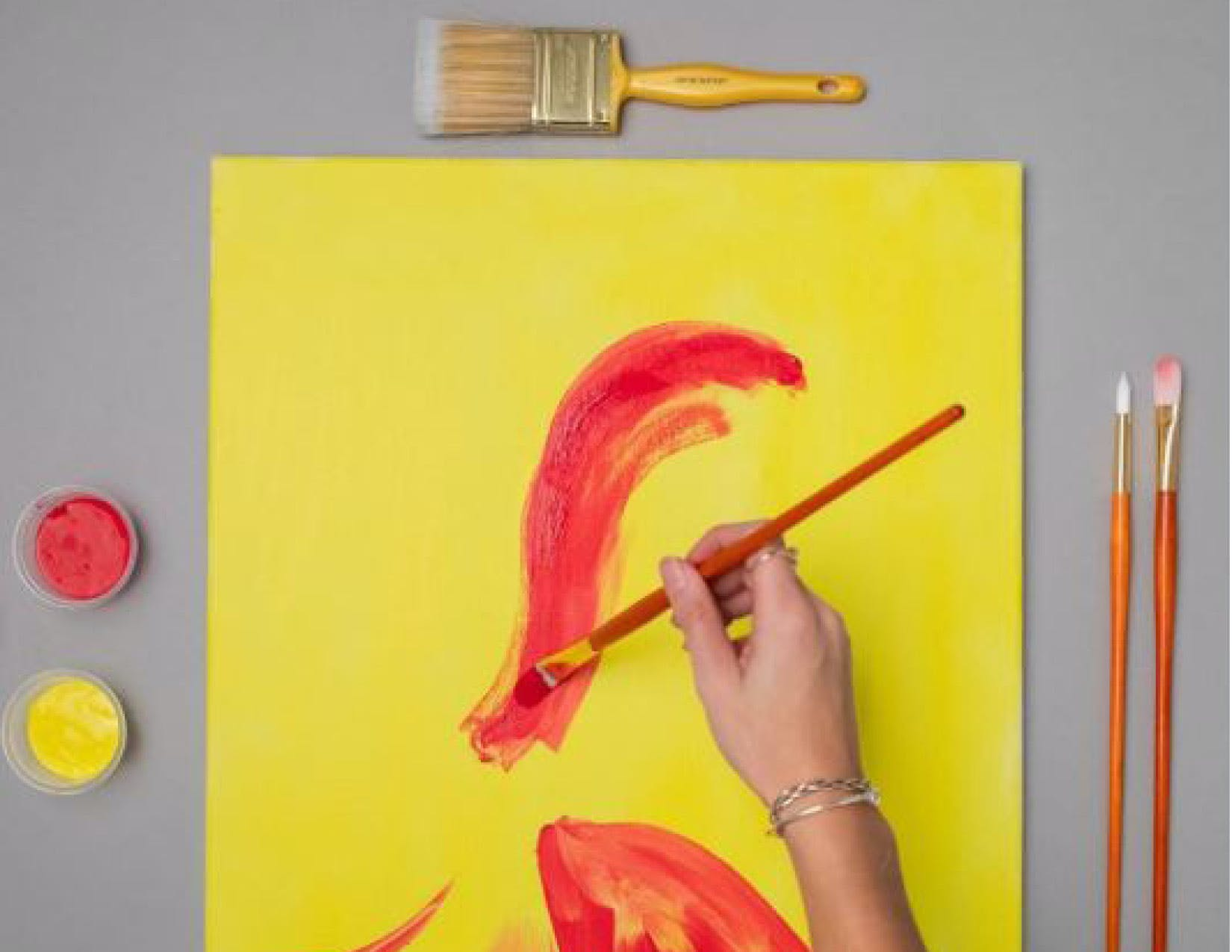 a person painting on a yellow paper