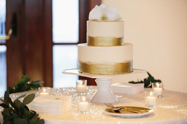 a two tier wedding cake with gold decorations