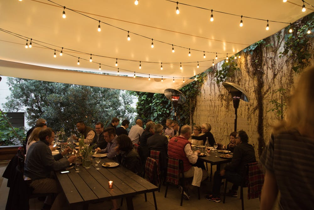 large tables set in the garden decorated with light bulbs on the ceiling with people seated on the table
