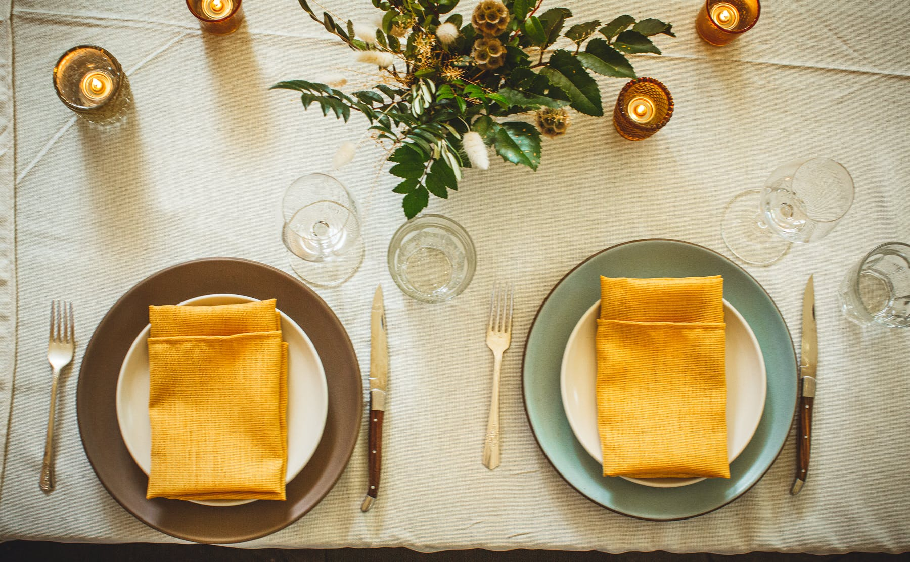 a table sit decorated with a yellow napkin on each plate