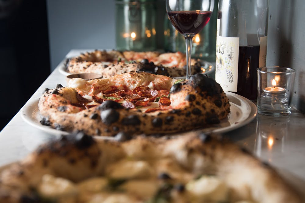 a close up of a plate of pizza and a glass of wine