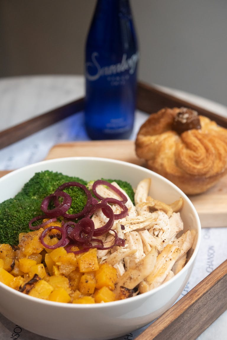 Organic chicken bowl, seasonal Kouign-Amann, and bottled water on a tray.