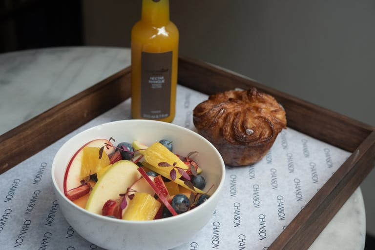 A bowl of fruit with a Kouign-Amann on a tray.