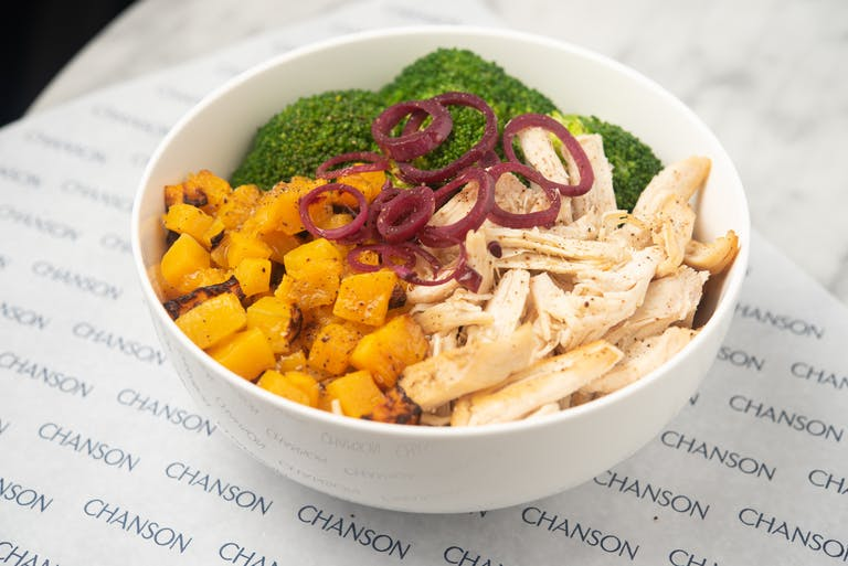 An organic chicken bowl with roasted squash and broccoli.