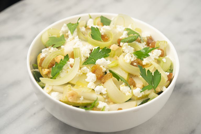 A pear and celery salad topped with goat cheese and hazelnuts.