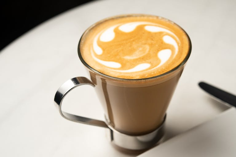 A close up of a handcrafted coffee beverage with fun design on top.