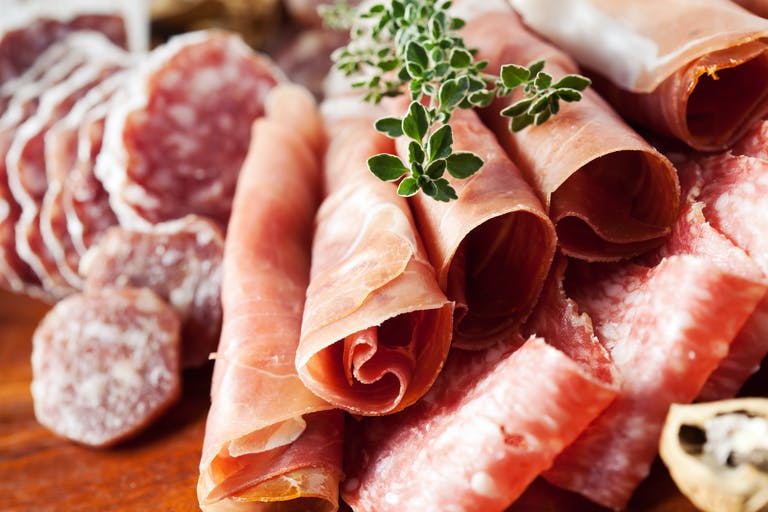 A close up of a charcuterie board of meats.