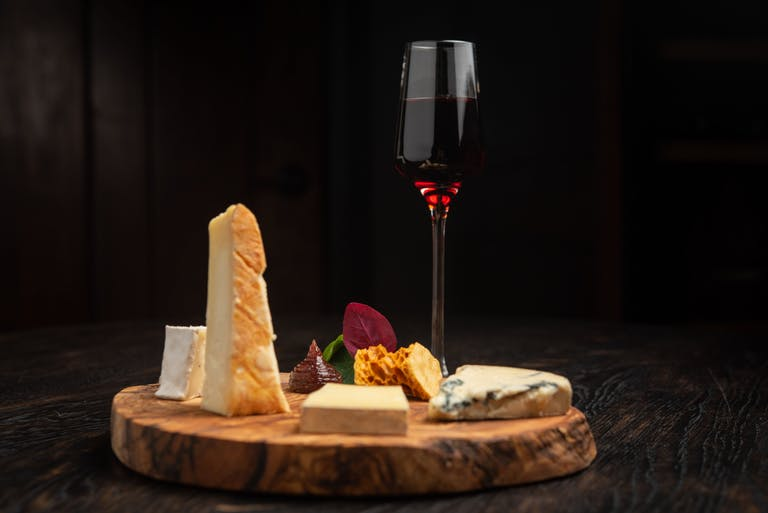 Artisan cheese platter with glass of wine.