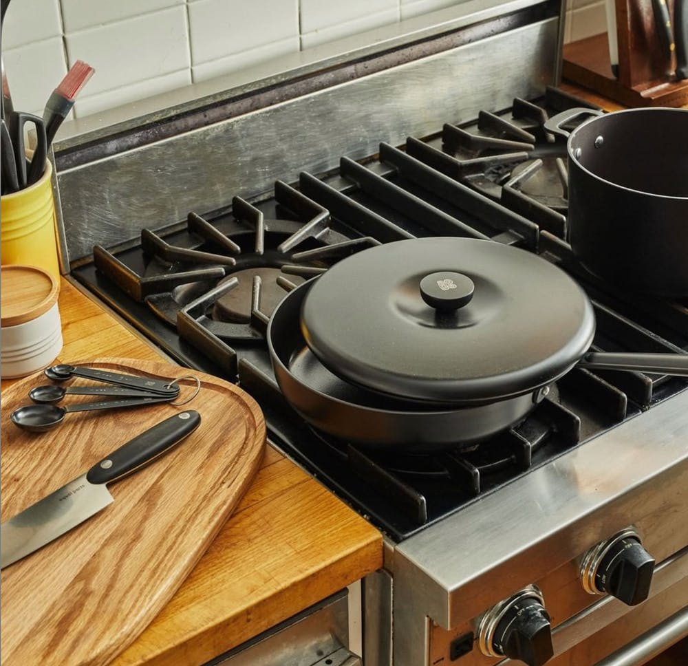 a black pan on a stove top oven sitting inside of a wooden table