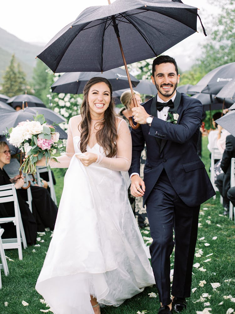 a couple of people that are standing in the rain holding an umbrella