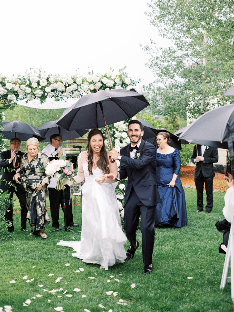 a group of people standing in the rain holding an umbrella
