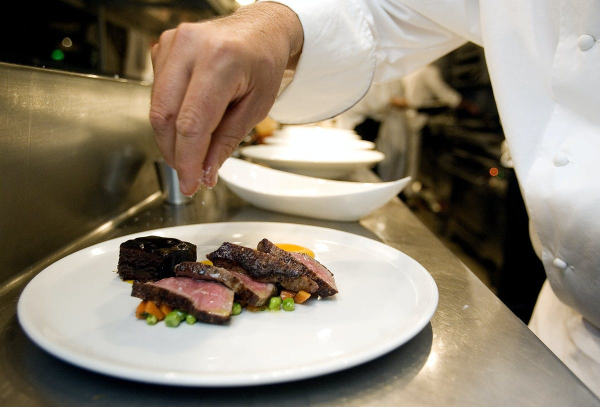 a man cutting food on a plate