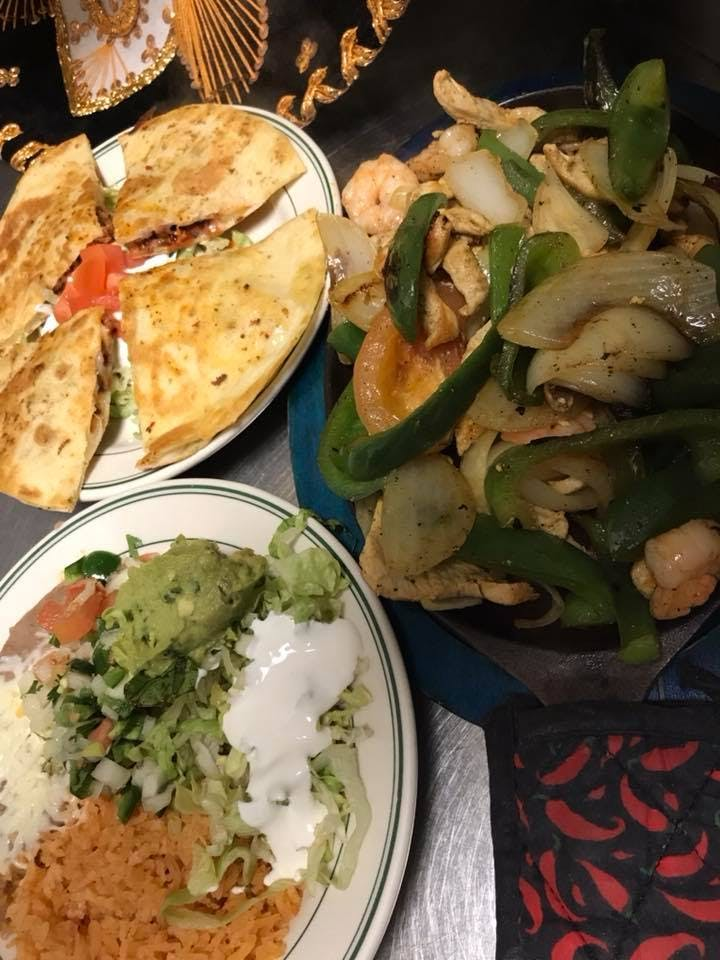 plates with quesadillas, salad and chicken with green rice