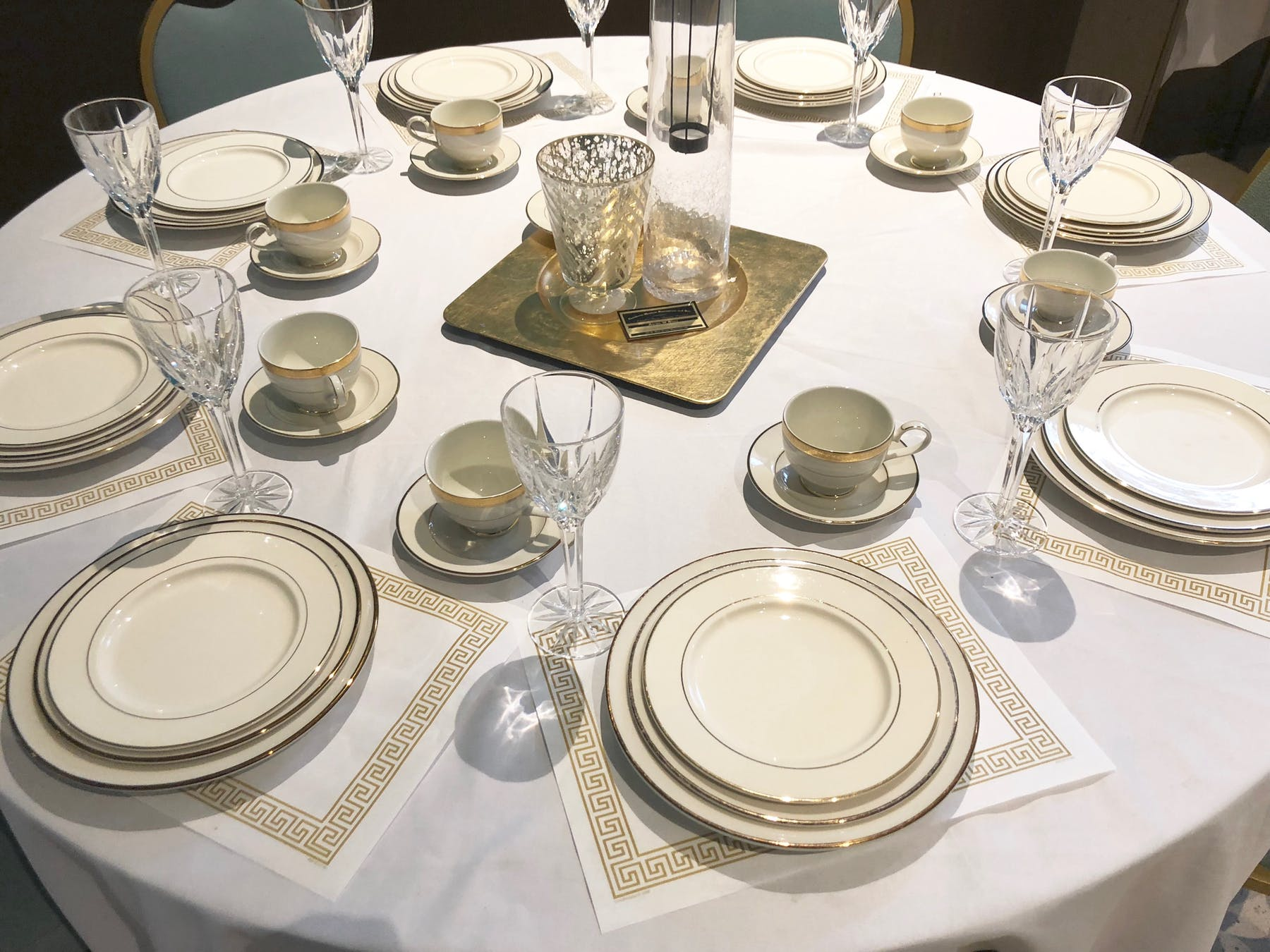 a dining table set with plates and glasses