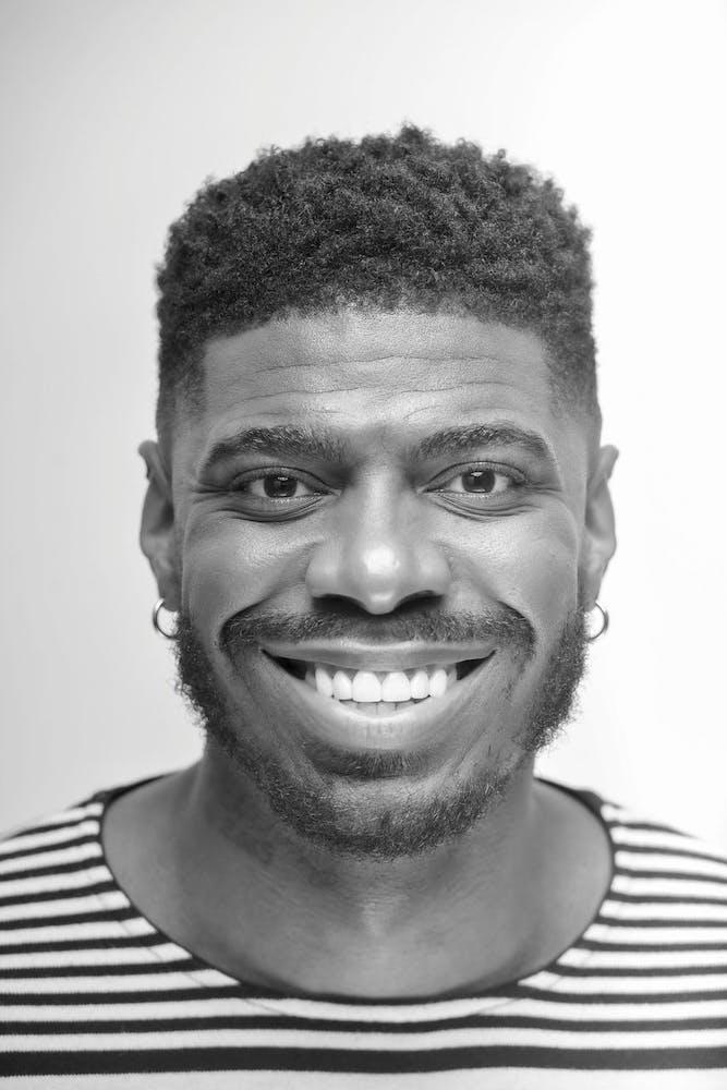 Jawan Jackson wearing a striped shirt and smiling at the camera
