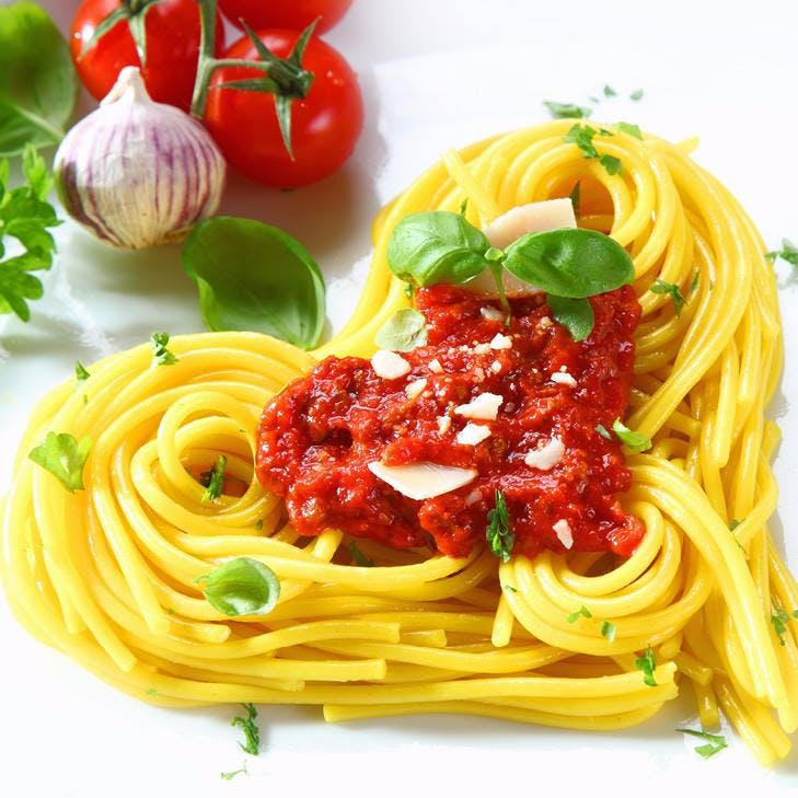 a closeup of a plate filled with pasta on a heart-shaped form next to some veggies