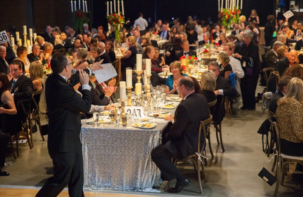 a group of people sitting at a table in front of a crowd