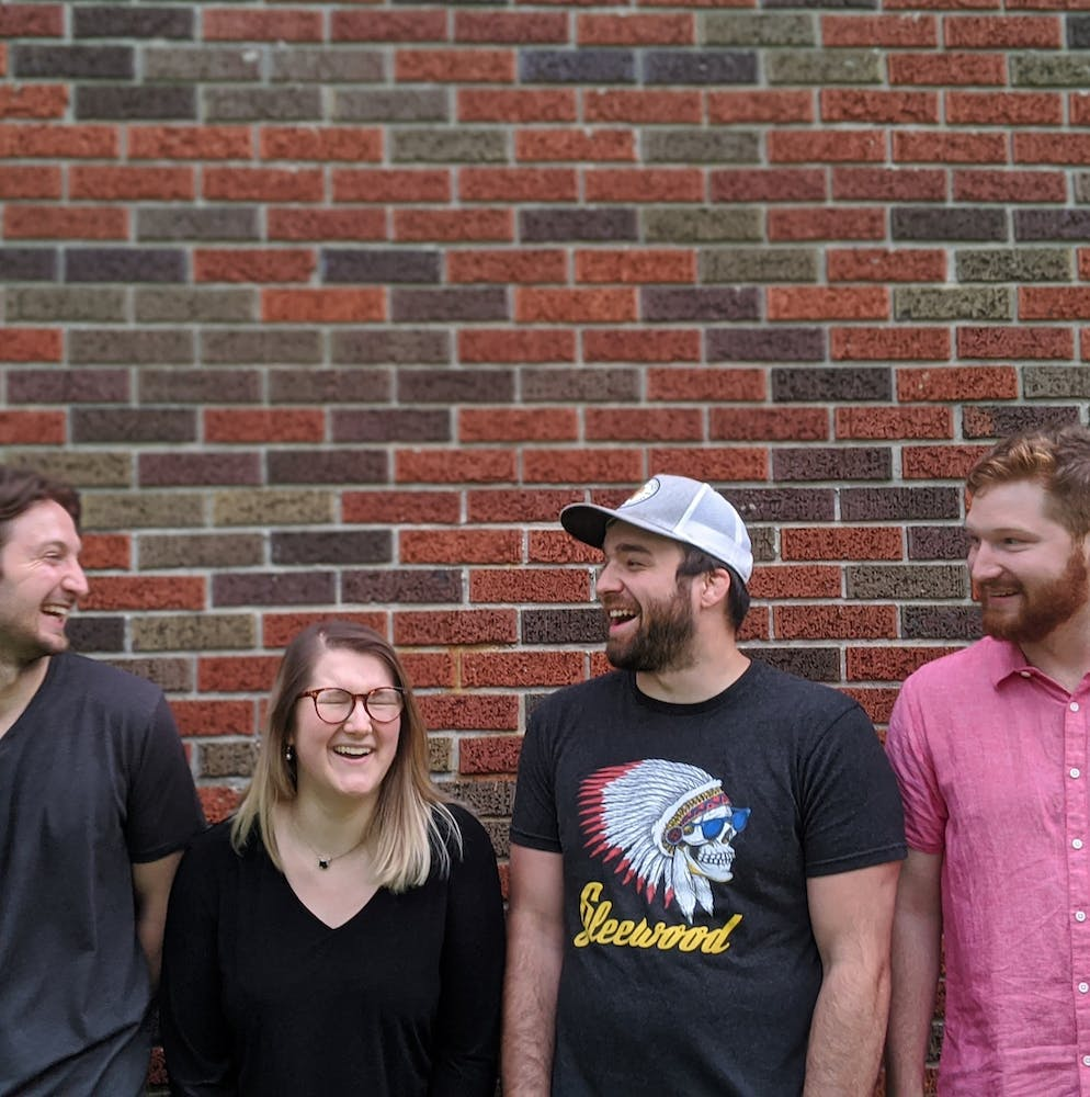 a group of people standing in front of a brick wall