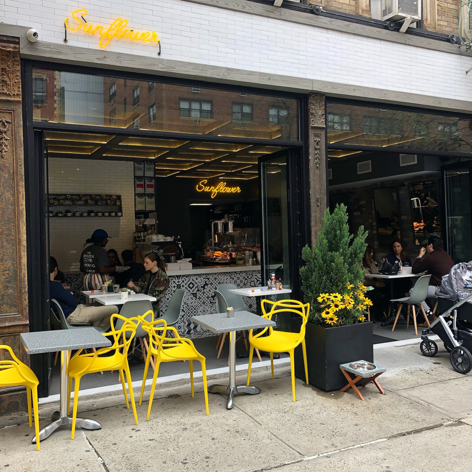 a group of people sitting at a table in front of a yellow building