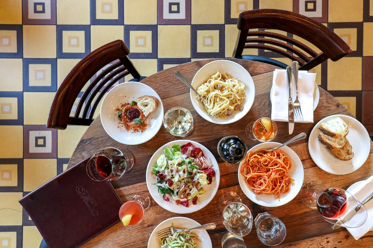 a full spread of food at Maialino - pastas, salad, sides, and wine