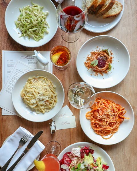 a table full of Italian dishes at Maialino, one of Eater's top Italian restaurants