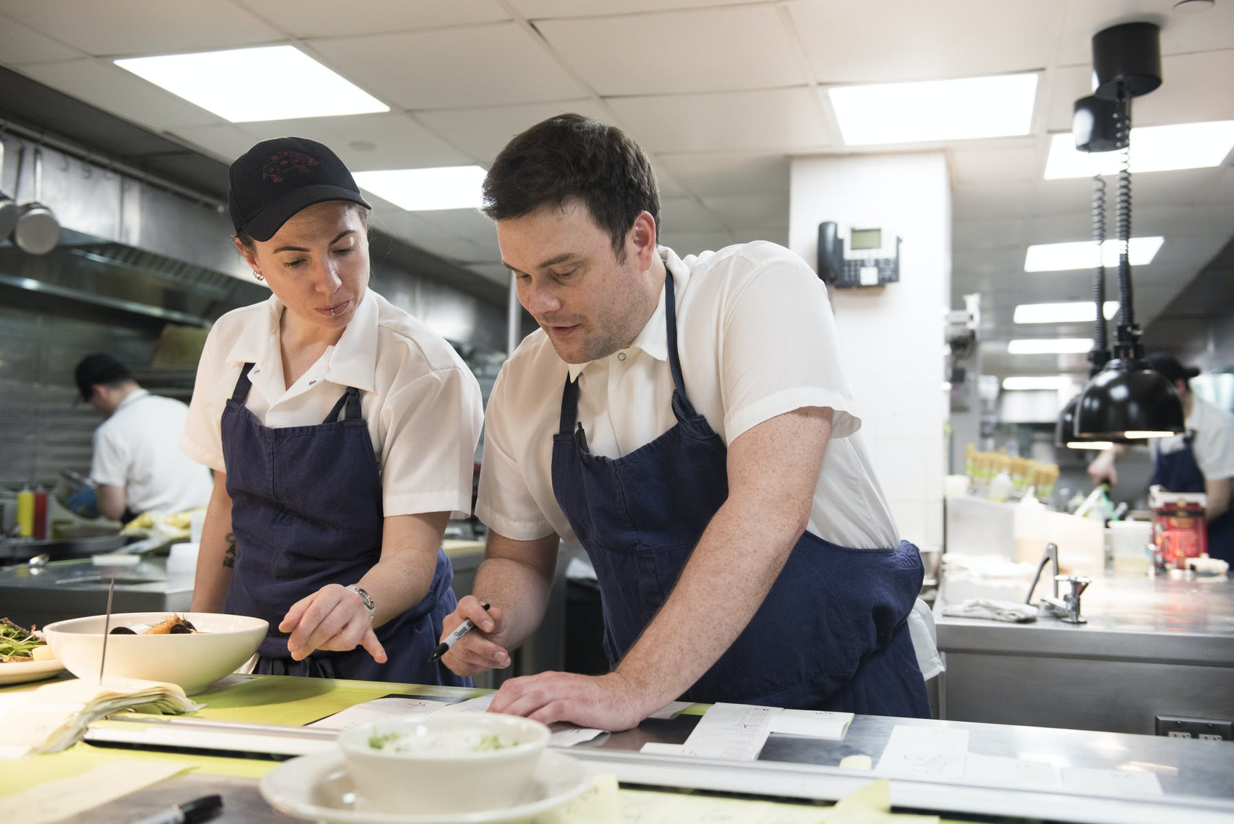 Chef de Cuisine Matt Spivey mentoring a colleague in the kitchen