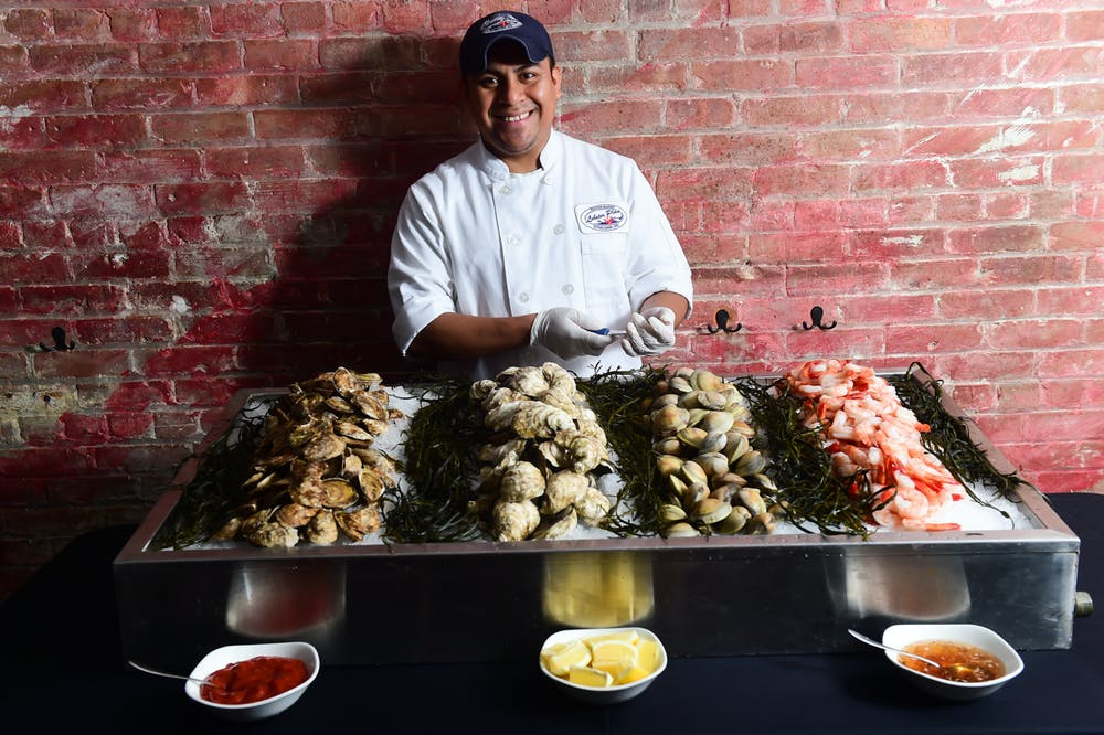 a man standing in front of a tray of food full of seafood