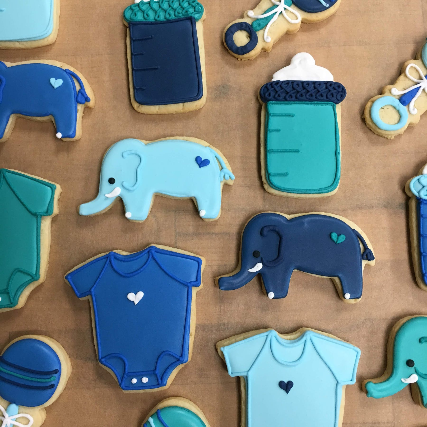 various shades of blue for bottles, onesies, elephants and rattles cookies
